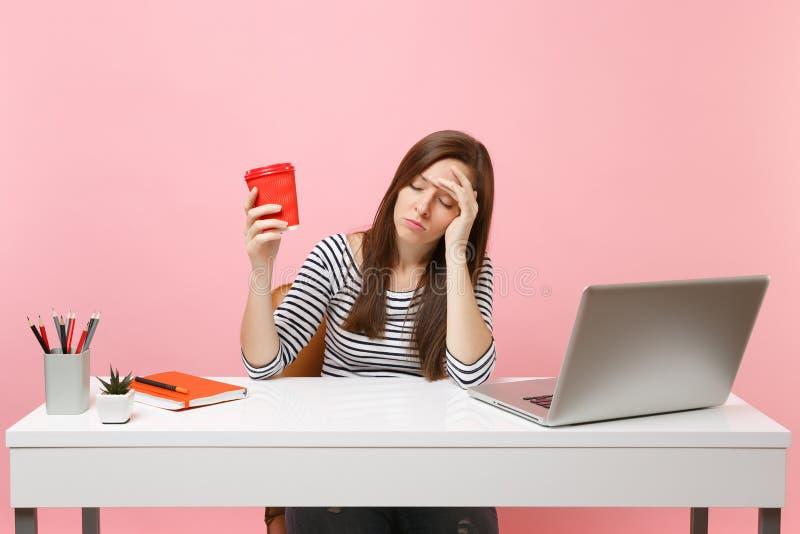 Mulher sonolento cansado dos jovens que inclina-se disponível guardando a xícara de café ou o chá quando trabalho e para sentar-s fotos de stock royalty free