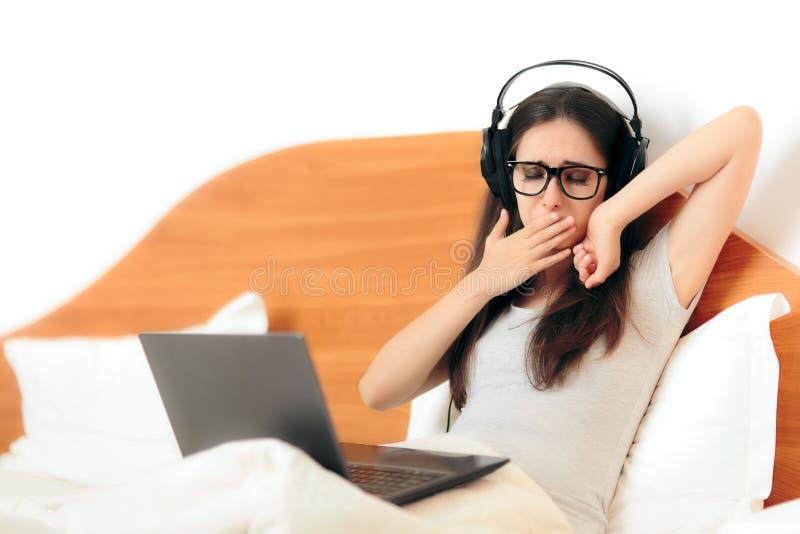 Mulher sonolento de bocejo com fones de ouvido e portátil fotografia de stock royalty free