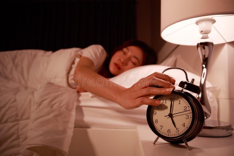 Mulher sonolento na cama com mão de alargamento fechado dos olhos aos clo do alarme fotos de stock