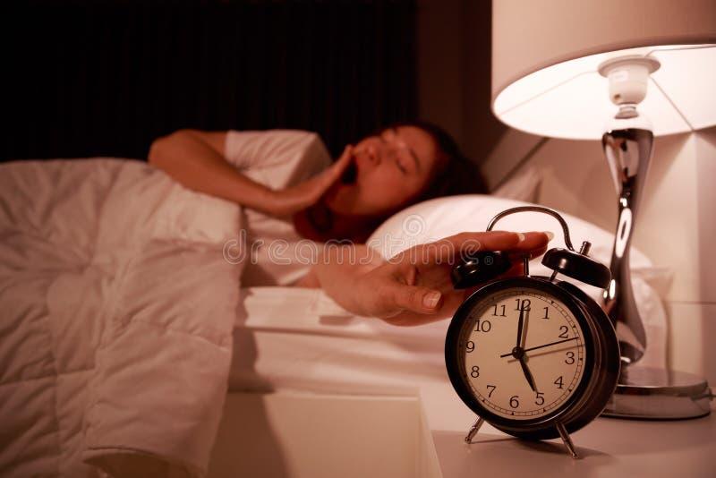 Mulher sonolento na cama com mão de alargamento fechado dos olhos aos clo do alarme fotografia de stock royalty free
