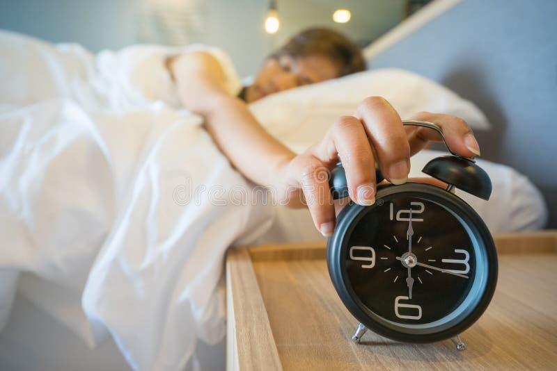 Mulher sonolento na cama que comuta fora do despertador imagens de stock royalty free