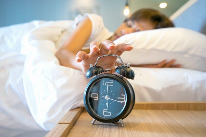 Mulher sonolento na cama que comuta fora do despertador, foco seletivo fotografia de stock