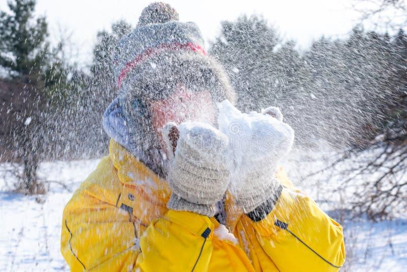 Mulher soprando neve de suas luvas fotografia de stock