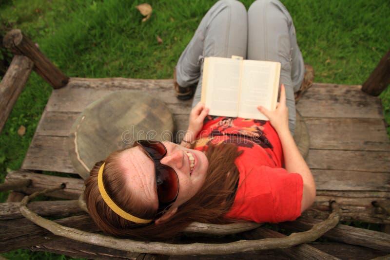 A mulher sorri ao ler um livro em um banco original imagens de stock royalty free