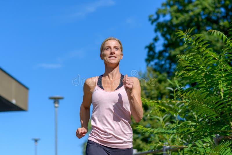 Mulher sorrindo enquanto corre ao ar livre foto de stock royalty free