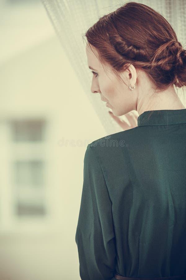 Mulher sozinha que olha com da espera da janela imagens de stock
