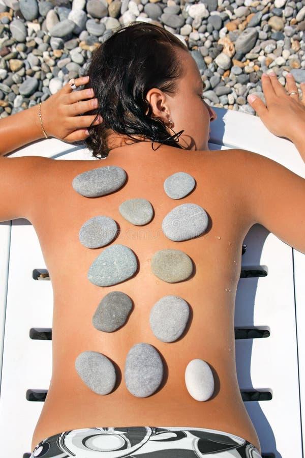 A mulher sunbathes na praia com pedras sobre para trás imagens de stock royalty free