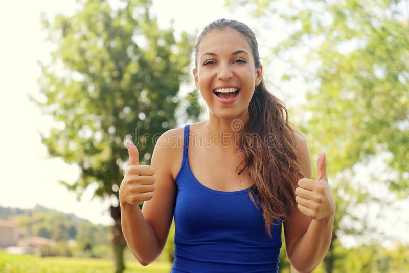 Mulher super! Retrato da menina do vencedor que mostra os polegares acima Mulher de sorriso positiva da aptidão exterior imagens de stock