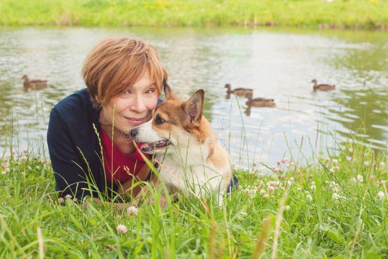 A mulher superior abraça seu cão no campo fotografia de stock royalty free