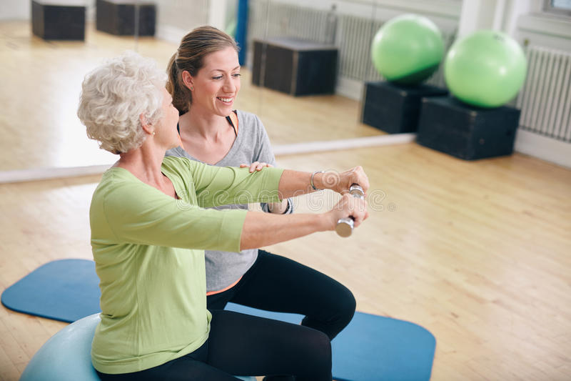 A mulher superior ajudou pelo instrutor pessoal no gym fotografia de stock royalty free