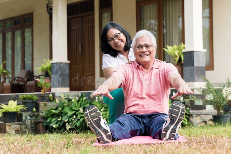 Mulher superior alegre que ajuda seu sócio durante a sessão do exercício foto de stock royalty free