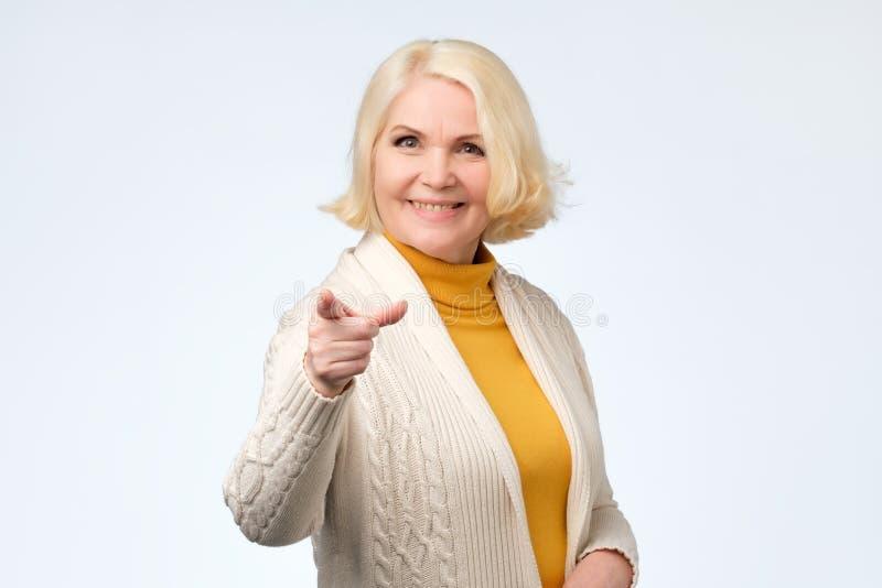 Mulher superior alegre que aponta o dedo na câmera fotos de stock