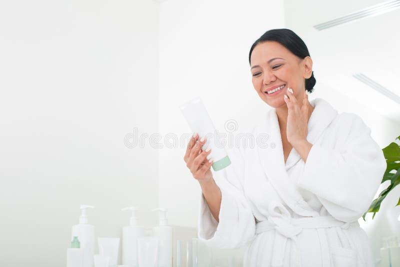 Mulher superior alegre que usa o cosmético no centro do bem-estar fotografia de stock royalty free