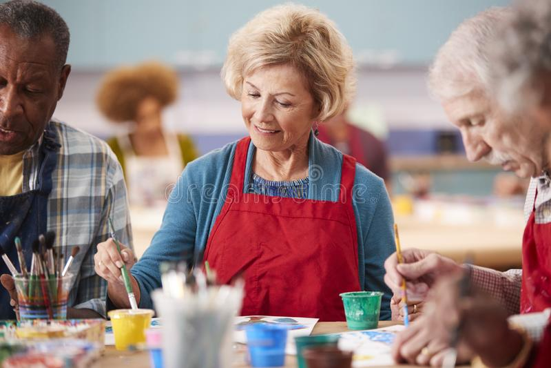 Mulher superior aposentada que atende a Art Class In Community Centre fotografia de stock