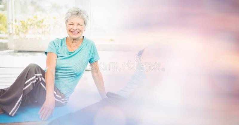 Mulher superior apta que exercita na classe da ioga foto de stock