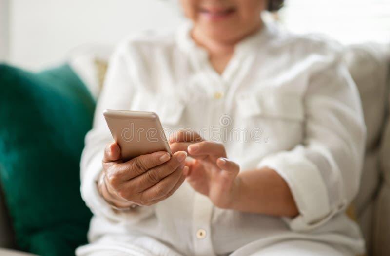 Mulher superior asiática feliz que usa o telefone esperto em sua casa foto de stock