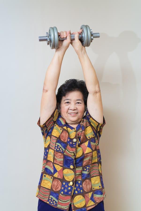 Mulher superior asiática forte que levanta peso, no tiro do estúdio, o speci fotos de stock