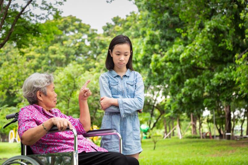 Mulher superior asiática na cadeira de rodas irritada, pontos seu dedo, advertindo de pouca menina da criança no parque exterior, foto de stock