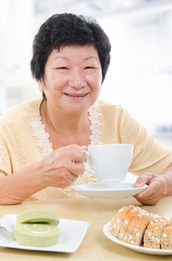 Mulher superior asiática que come o pequeno almoço fotografia de stock