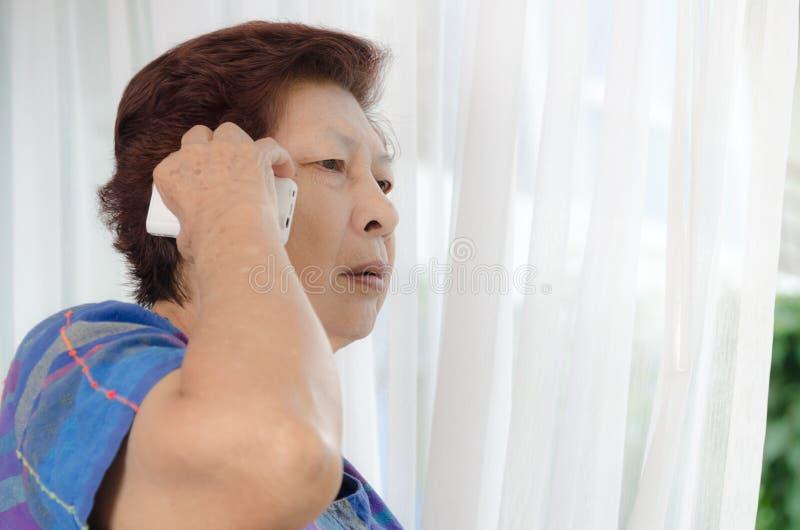 Mulher superior asiática que usa um telefonema perto da janela em casa imagens de stock royalty free