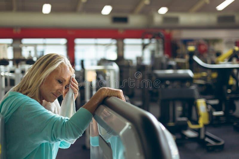 Mulher superior ativa cansado que limpa a toalha suada no estúdio da aptidão imagens de stock