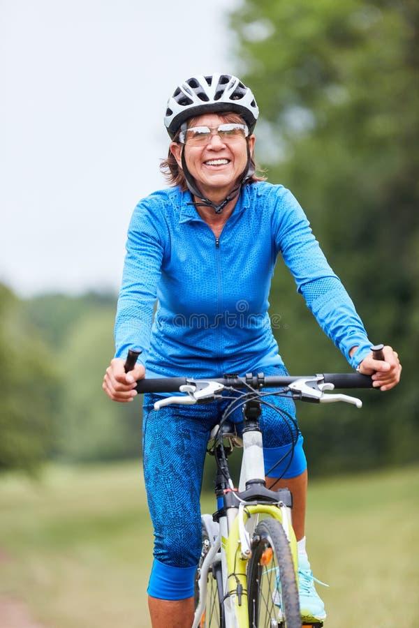 A mulher superior ativa est? fazendo um passeio da bicicleta imagem de stock royalty free