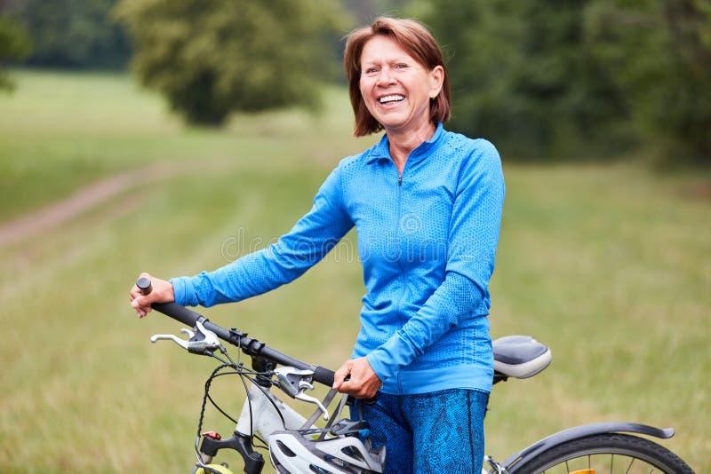 A mulher superior ativa est? fazendo um passeio da bicicleta fotos de stock