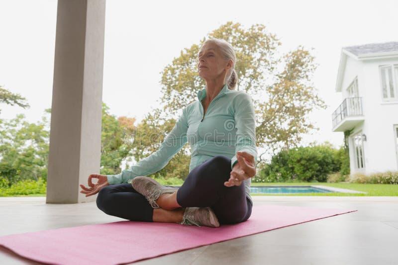 Mulher superior ativa que faz a ioga na esteira do exercício no patamar em casa fotografia de stock
