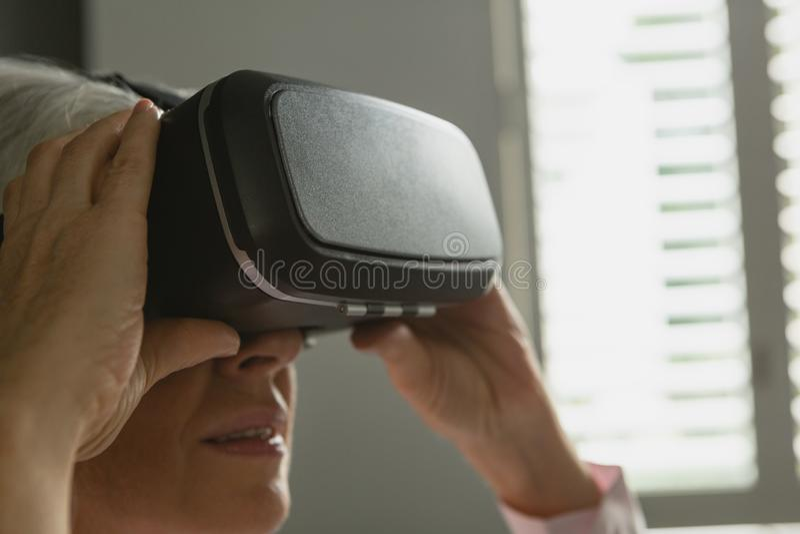 Mulher superior ativa que usa auriculares da realidade virtual na sala de visitas imagens de stock royalty free