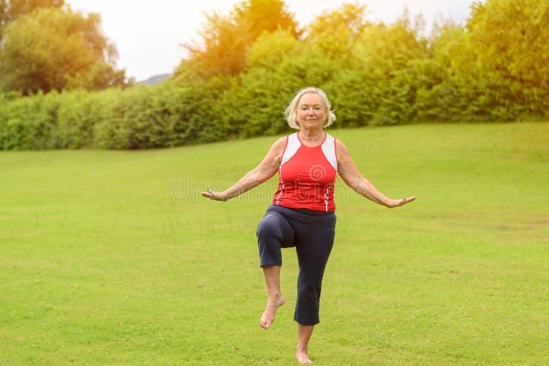 Mulher superior atlética que executa exercícios do equilíbrio foto de stock