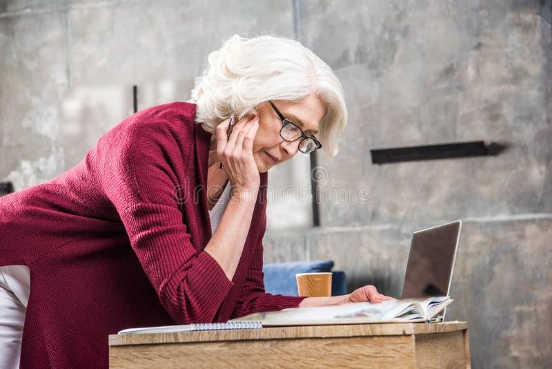 Mulher superior atrativa no livro de leitura dos monóculos ao sentar-se na mesa com portátil imagem de stock royalty free