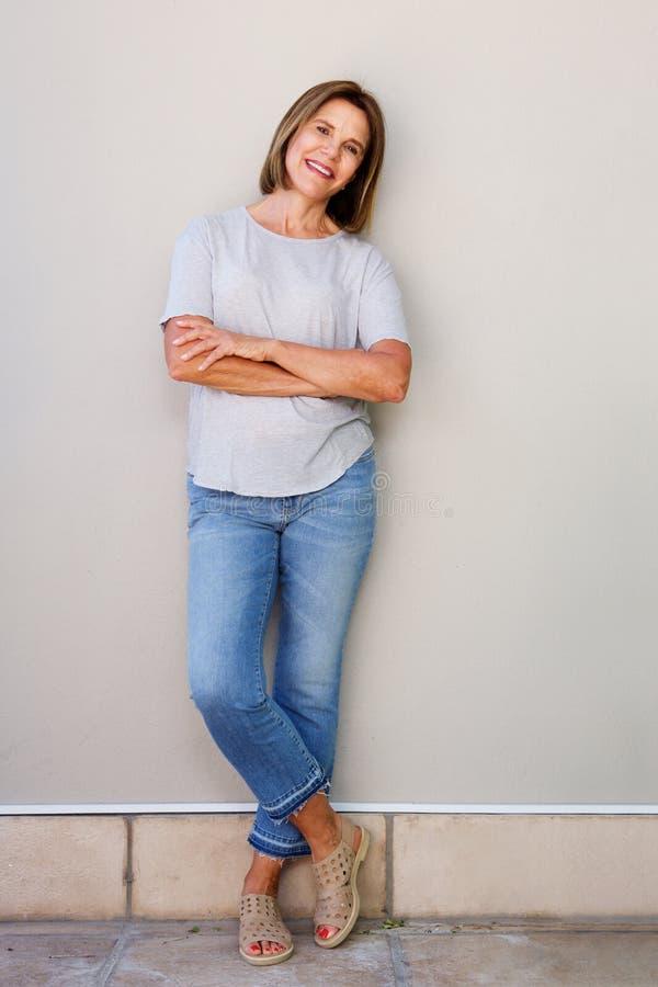 Mulher superior atrativa que sorri com os braços cruzados imagem de stock