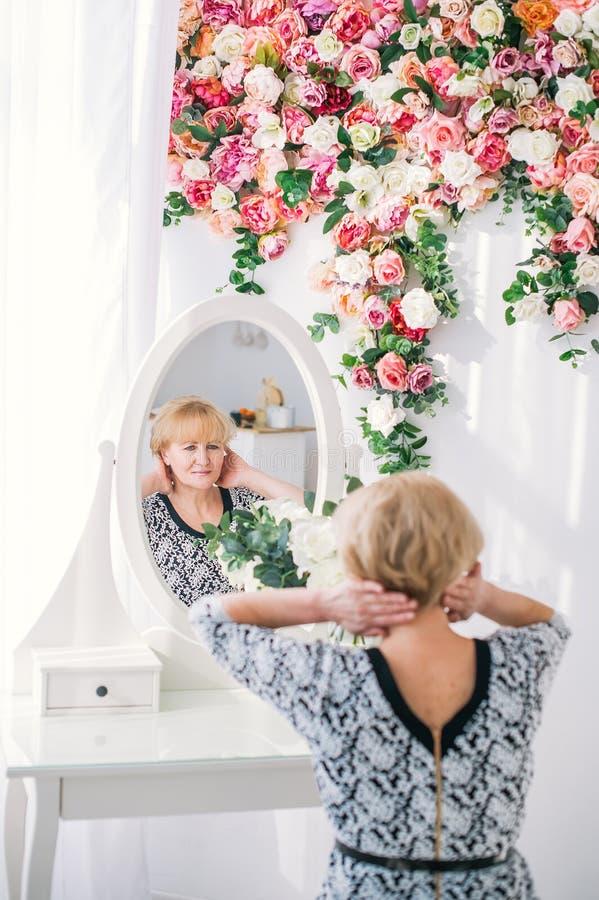 Mulher superior bonita com o cabelo louro que olha a reflexão no espelho no estúdio branco com flores coloridas fotografia de stock