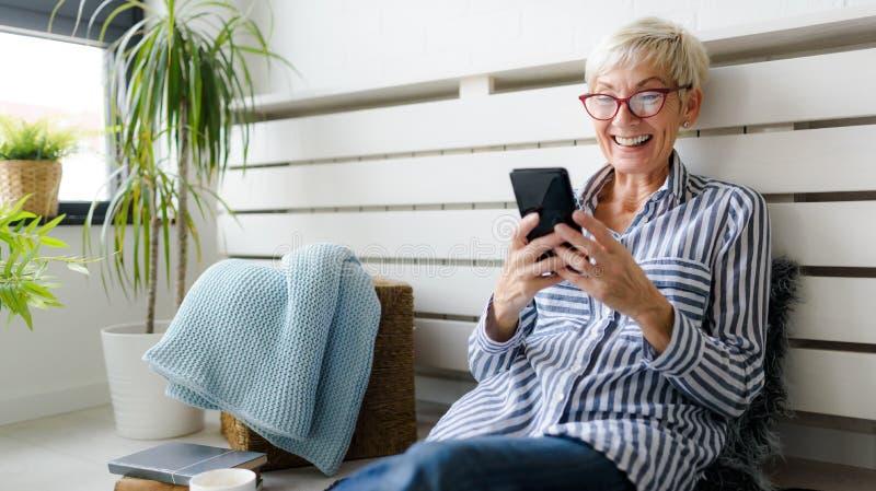 Mulher superior bonita de sorriso que usa a tabuleta digital em casa fotos de stock royalty free