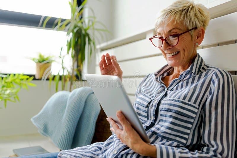 Mulher superior bonita de sorriso que usa a tabuleta digital em casa fotos de stock