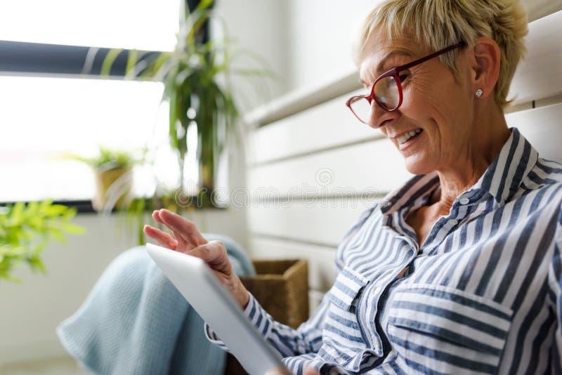 Mulher superior bonita de sorriso que usa a tabuleta digital em casa foto de stock