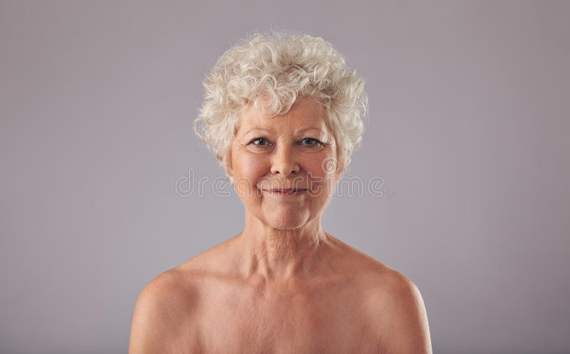 Mulher superior bonita descamisado contra o fundo cinzento foto de stock royalty free