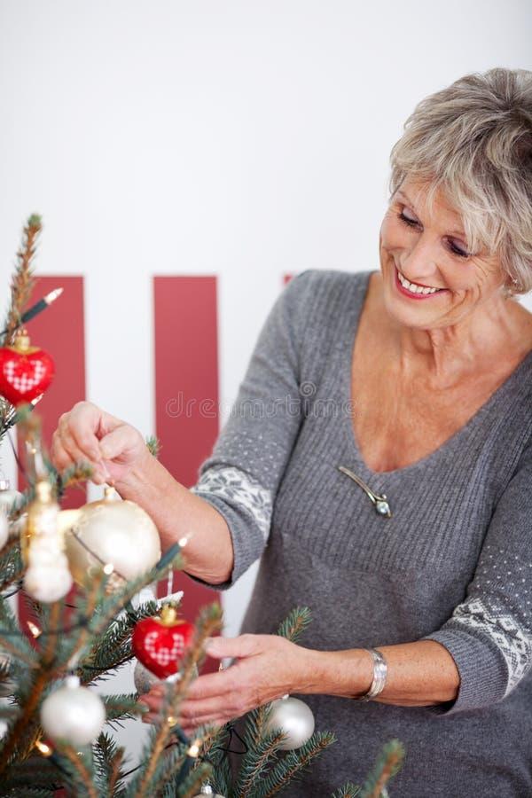 Mulher superior bonita que decora uma árvore foto de stock