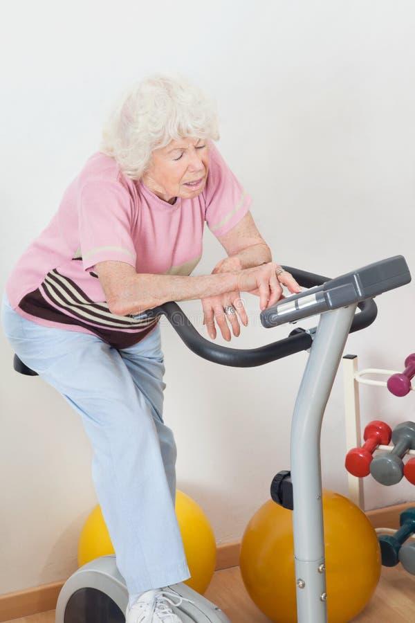 Mulher superior cansado que exercita na bicicleta fotografia de stock royalty free