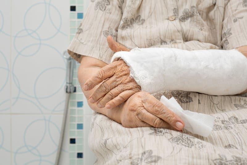 Mulher superior com braço quebrado usando o toalete fotos de stock