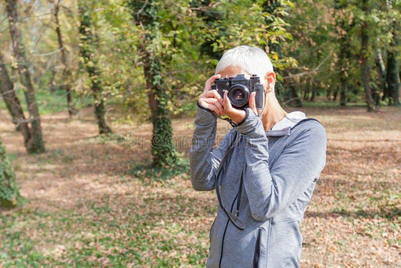 Mulher superior com a câmera retro exterior foto de stock