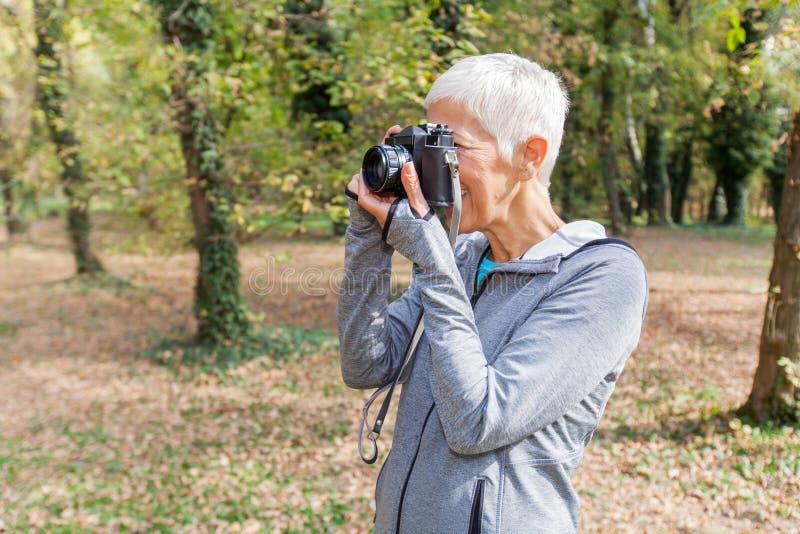 Mulher superior com a câmera retro exterior imagens de stock royalty free