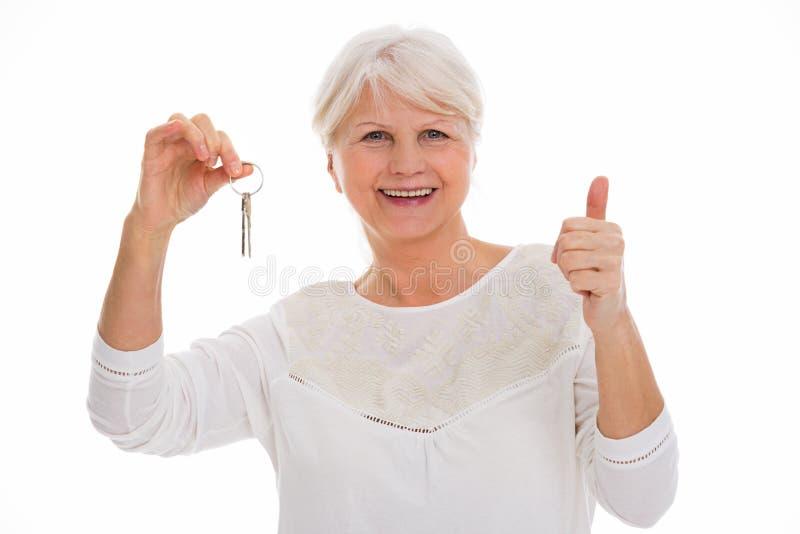 Mulher superior com chaves à casa nova fotografia de stock