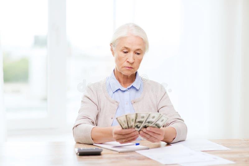 Mulher superior com dinheiro e papéis em casa imagem de stock
