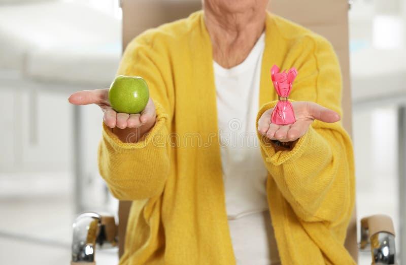 Mulher superior com entre a maçã e os doces no hospital, close up imagem de stock royalty free