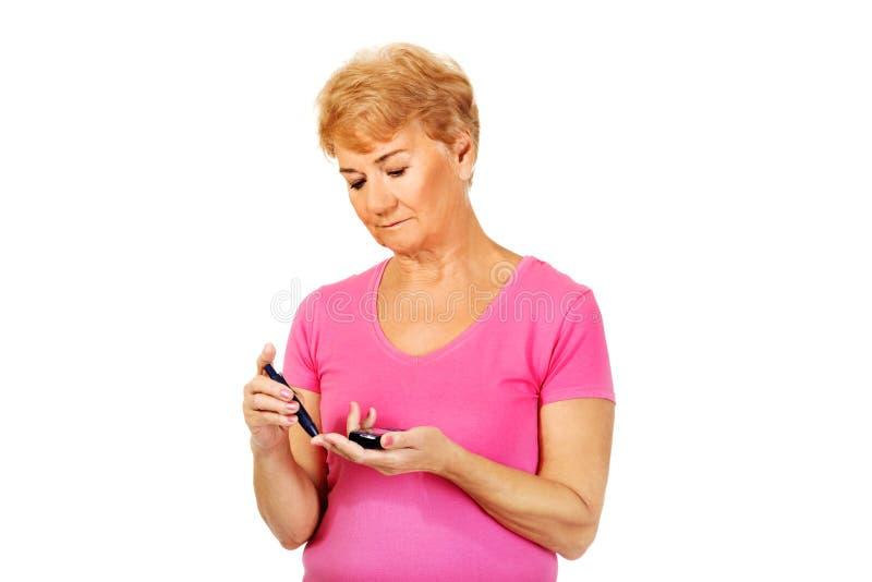 Mulher superior com glucometer que verifica o nível do açúcar no sangue fotos de stock