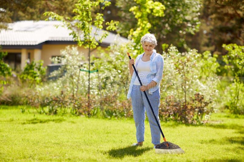 Mulher superior com o ancinho do gramado que trabalha no jardim imagem de stock royalty free