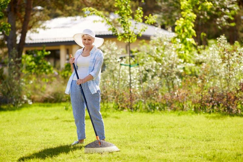 Mulher superior com o ancinho do gramado que trabalha no jardim imagem de stock