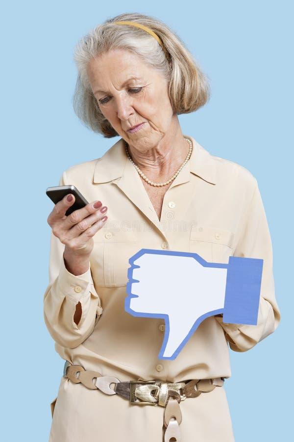 Mulher superior com o telemóvel que mantem o botão falsificado do desagrado contra o fundo azul fotografia de stock
