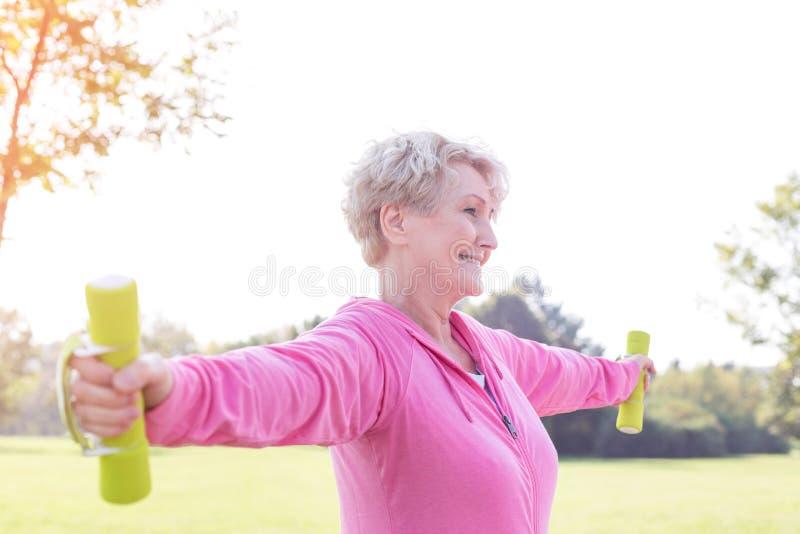 Mulher superior com pesos de levantamento estendidos dos braços no parque fotografia de stock